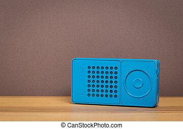 old radio on wooden table with color wall background