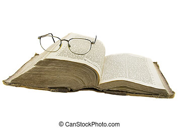 Vintage open book bible open and glasses on it isolated over...