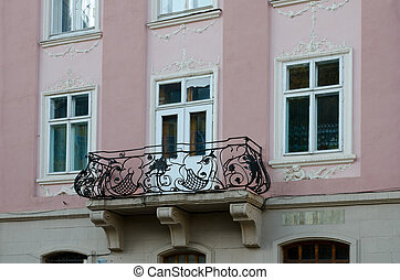 Vintage open wrought-iron balconies on a background of moldings window