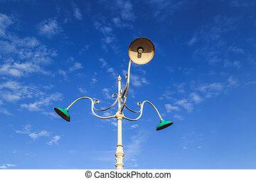 Vintage outdoor lamp on blue sky background