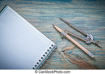 Vintage pair of compasses pencil checked copybook on wooden boar