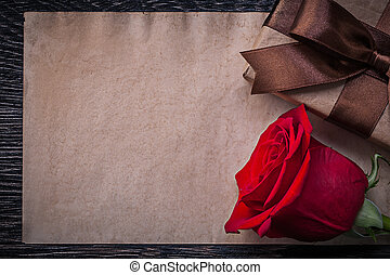 Vintage paper red rose giftbox on wooden board