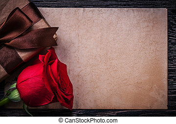 Vintage paper red rose wrapped giftbox on wooden board