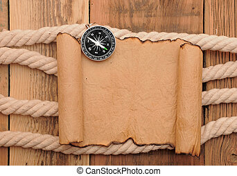 Vintage paper scroll with compass and rope on old wooden boards