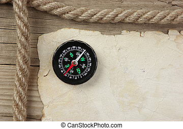 Vintage paper with compass and rope on old wooden boards