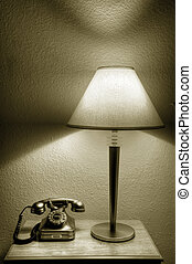 Vintage phone next to lamp on night stand in a hotel room