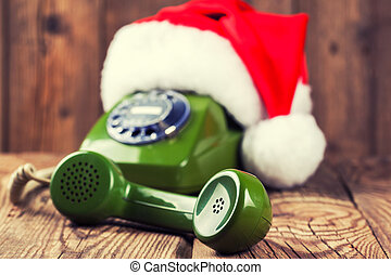 vintage phone with Santa's hat on wooden background