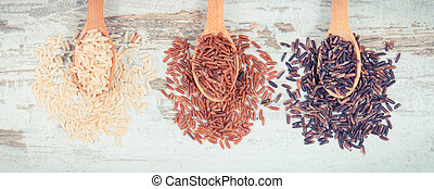 Vintage photo, Brown, black and red rice on wooden spoons, healthy gluten free food concept