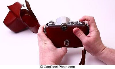 Vintage photo camera isolated on a white background in man hands. Old retro camera.