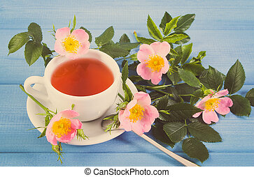 Vintage photo, Cup of tea and wild rose flower on blue boards