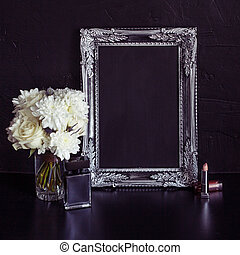 Vintage photo frame and flowers on a black textured ...