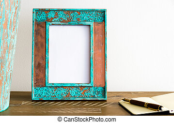 Vintage photo frame on wooden table over white wall background
