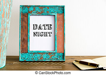 Vintage photo frame on wooden table with text DATE NIGHT