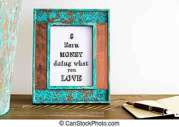 Vintage photo frame on wooden table with text EARN MONEY DOING WHAT YOU LOVE