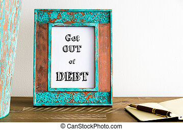 Vintage photo frame on wooden table with text GET OUT OF DEBT