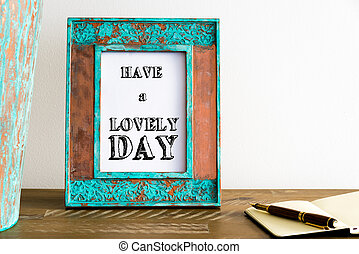 Vintage photo frame on wooden table with text HAVE A LOVELY DAY