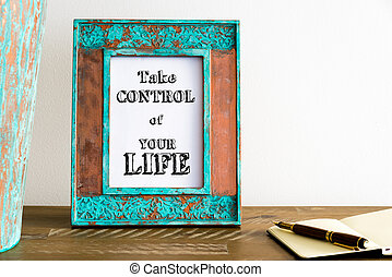 Vintage photo frame on wooden table with text TAKE CONTROL OF YOUR LIFE
