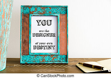 Vintage photo frame on wooden table with text YOU ARE THE DESIGNER OF YOUR OWN DESTINY
