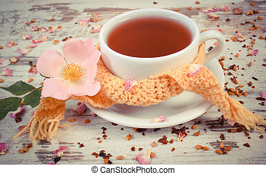 Vintage photo, Hot tea with wild rose flower in cup wrapped scarf