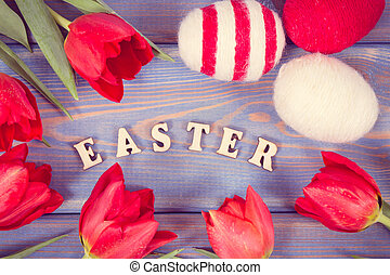 Vintage photo, Inscription Easter, fresh red tulips and eggs wrapped woolen string on boards, festive decoration