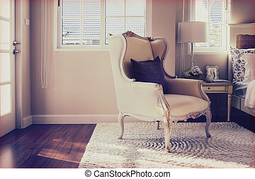 vintage photo of classic chair with brown pillow on carpet in luxury bedroom interior