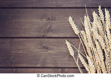 Vintage photo of ears of wheat lying on a wooden desk