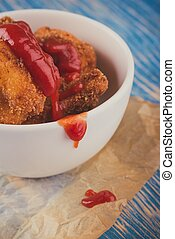 Vintage photo of few pieces of fried cauliflower with ketchup