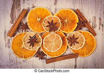 Vintage photo, Slices of dried lemon, orange and spices on old wooden background