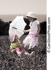 Vintage photo with two little girls with an umbrella on lawn, collage
