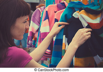 Vintage photo, Woman shopping clothes on stall at the bazaar