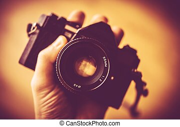 Vintage Photography Concept. Vintage Analog Camera in a Hand...