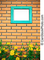 Vintage picture frame on brick wall with yellow flower