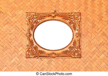 Vintage picture frame on woven wood wall