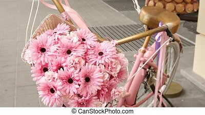 Vintage pink bicycle with flower basket close-up