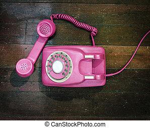 vintage pink phone on a old wooden floor