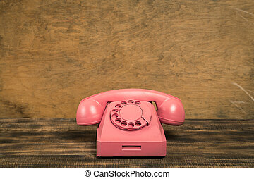 Vintage pink telephone on wooden table with color wall background