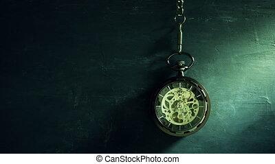 Vintage pocket watch hanging on black chalkboard. - Time...
