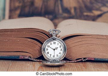 Vintage pocket watch on  books.