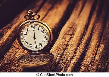 vintage pocket watch on grunge wooden board