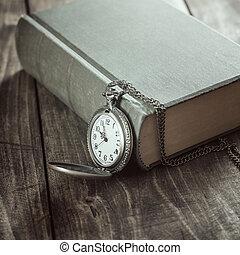 Vintage pocket watch on old books.