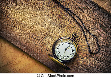 vintage pocket watch on wood board background