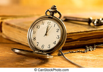 Vintage pocket watch on wooden surface against old book