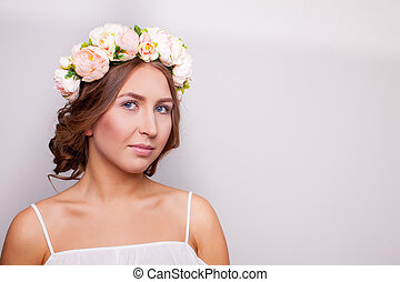 Vintage portrait of a beautiful girl with flowers on her head on a white background.