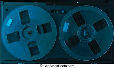 Vintage professional analog reel to reel audio magnetic tape recorder illuminated by colorful neon lights. Reels are moving, record or music is playing. Close up. Slow motion