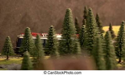 Vintage railway diesel locomotive moving through forest. Toy railway vehicle in motion.