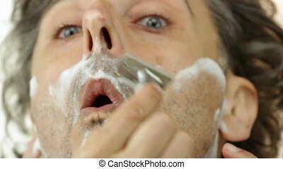 vintage razor - Man shaving his cheek using vintage razor
