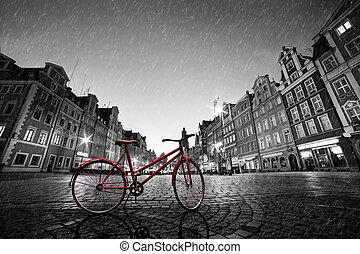 Vintage red bike on cobblestone historic old town in rain. Wroclaw, Poland.