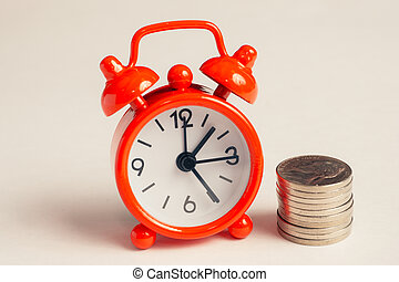 Vintage red clock next to a stack of coins.