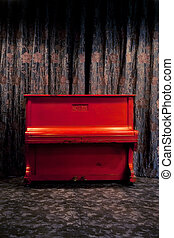 Vintage red piano in dark theatre or nightclub interior over floral ornated curtains background
