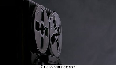 Vintage reel to reel tape recorder on dark background smoky studio with backlight. Man hand includes black old tape recorder. Close up. Slow motion